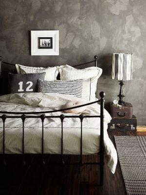 Industrial Chic Bedroom. Quarto De Casal Com Parede De Cimento Queimado E  Cabeceira De Ferro Antiga, Várias Almofadas E Decoração Em Cinza E Branco.