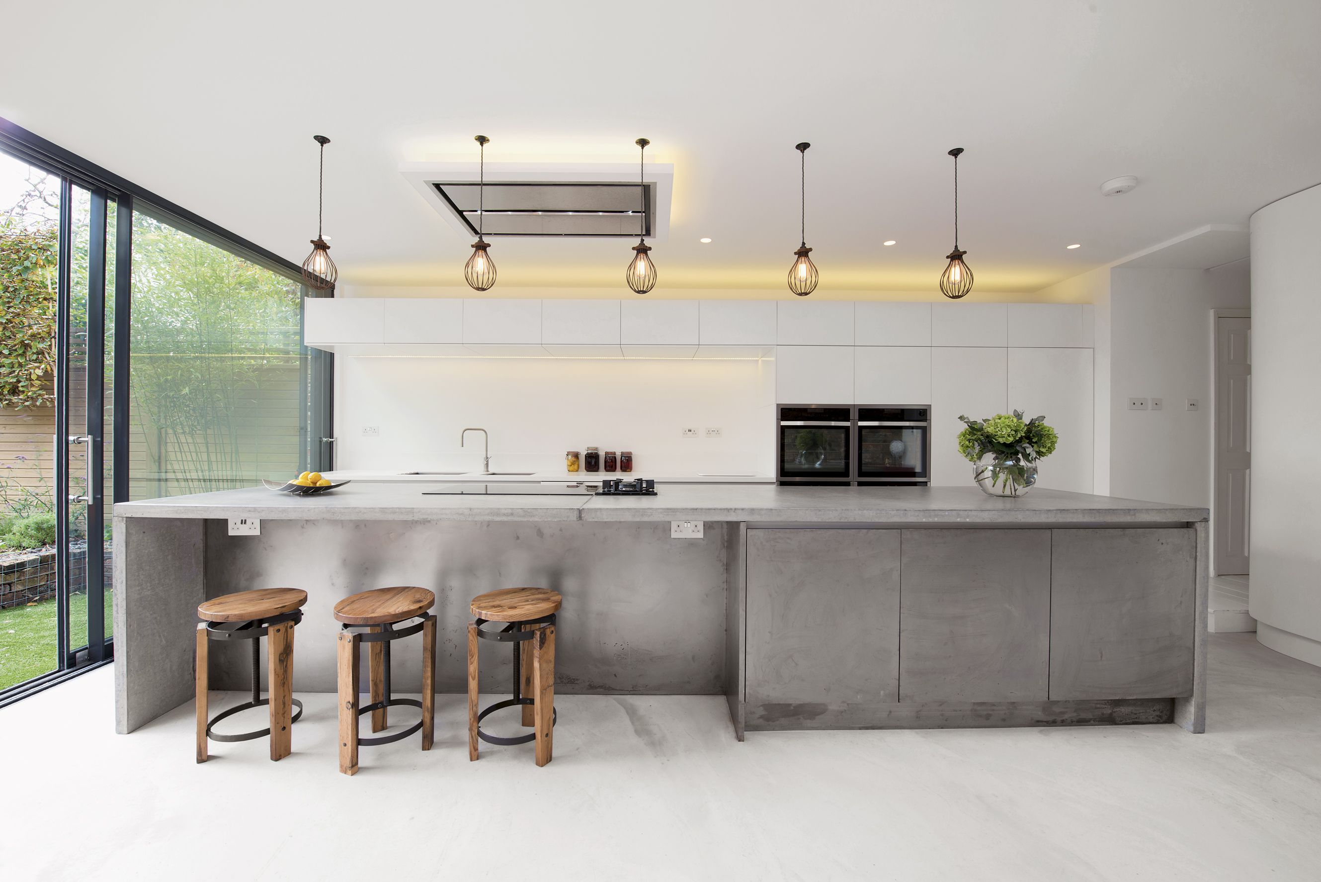 This Large Island Is Clad In Concrete And Is Paired With A Polished Concrete Floor Design B Concrete Kitchen Island Concrete Kitchen Industrial Style Kitchen