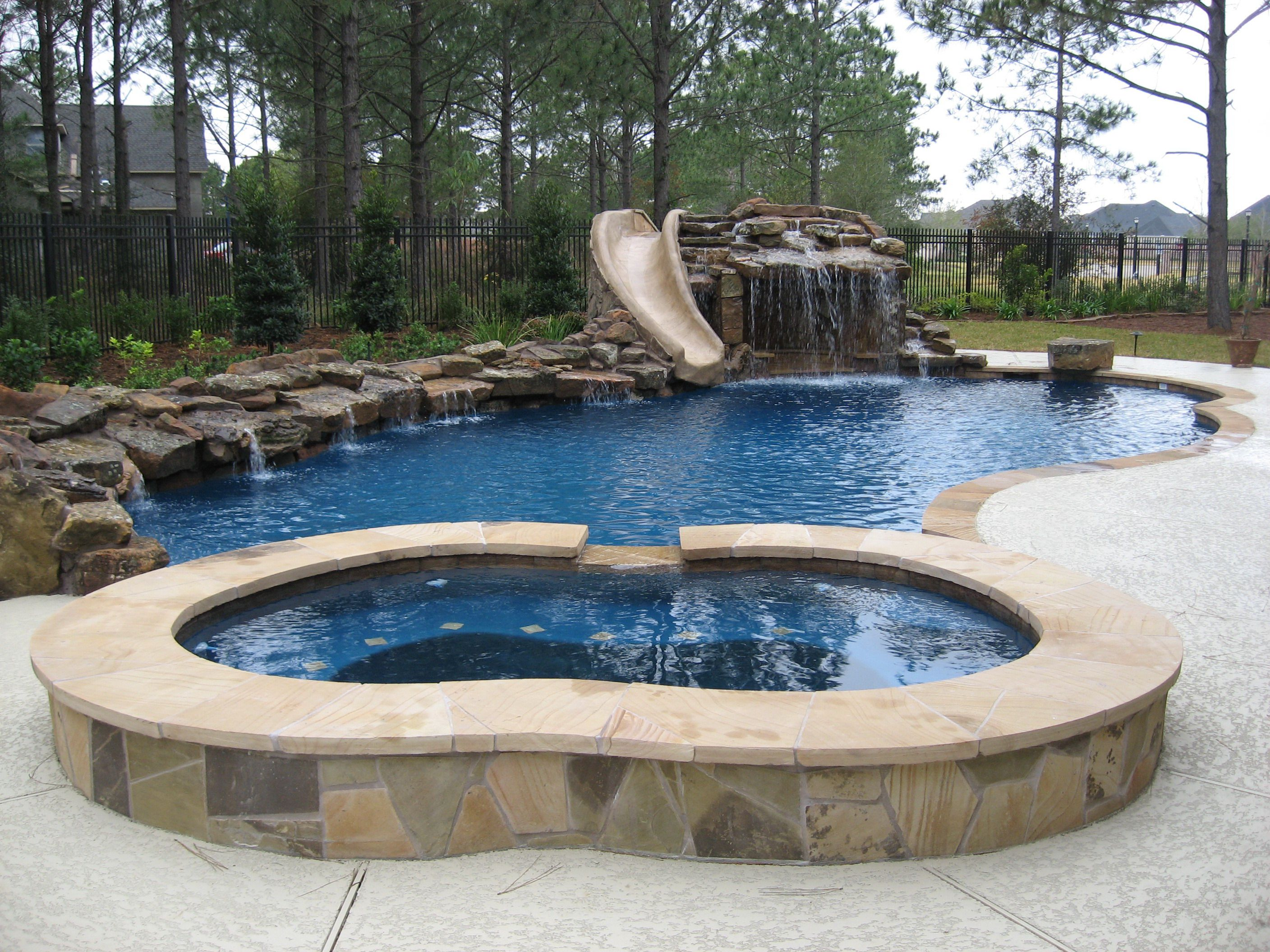 Gunite swimming pool with moss rock waterfall dive rock for Pool design omaha