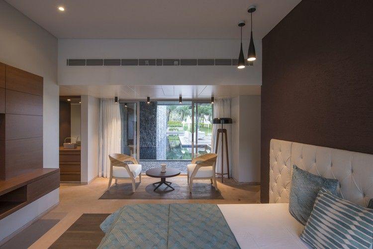 schlafzimmer sitzbereich braune wand blick garten wasserfall