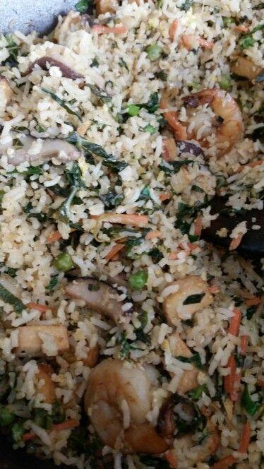 Fried rice with onions, peas, carrots, sesame ginger baked tofu, shrimp,  shrimp sambal, soy sauce, shitake mushrooms,  cauliflower leaves, white rice and scallions.