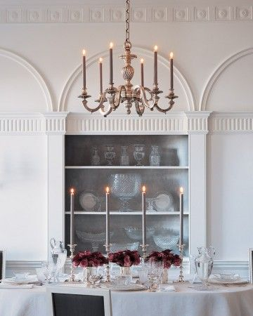 A multitude of candlesticks -- in this case, an even-numbered quartet -- gives some dimension and drama to the dining room table. Placing the candlesticks equidistantly along the table ensures a sense of balance still rules.