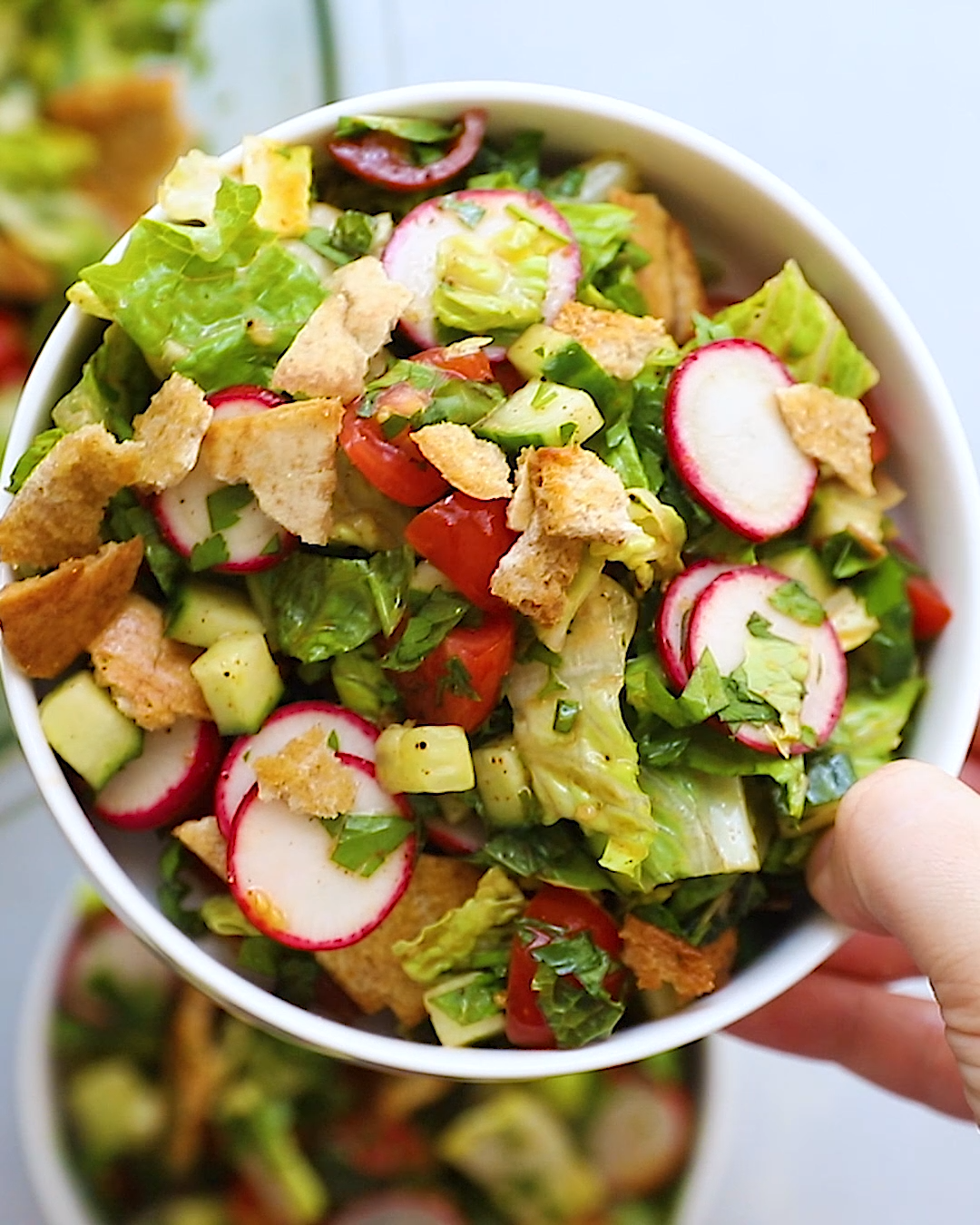 This delicious Middle Eastern fattoush salad has vegetables, fresh herbs, crispy pita bread, and a sumac dressing. Great as an appetizer or served with protein for a meal.