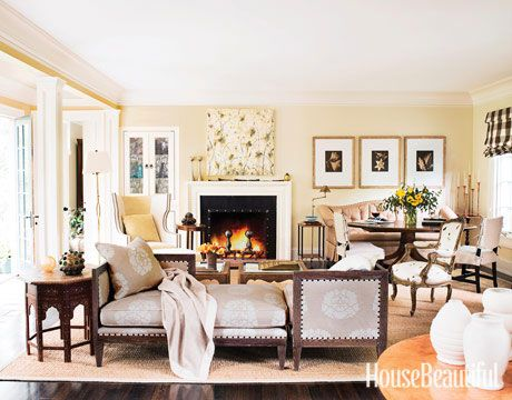 """The living room of this New Jersey house is made for entertaining: """"I can go from cocktails to dessert in the same space,"""" designer Frank DelleDonne says. He hosts small dinners at the round table, a reproduction of an 18th-century piece by Barton-Sharpe. The camelback sofa, three-piece """"sectional,"""" and coffee tables are by FD Interiors. Betsy Eby painting, Willis Lee photographs."""