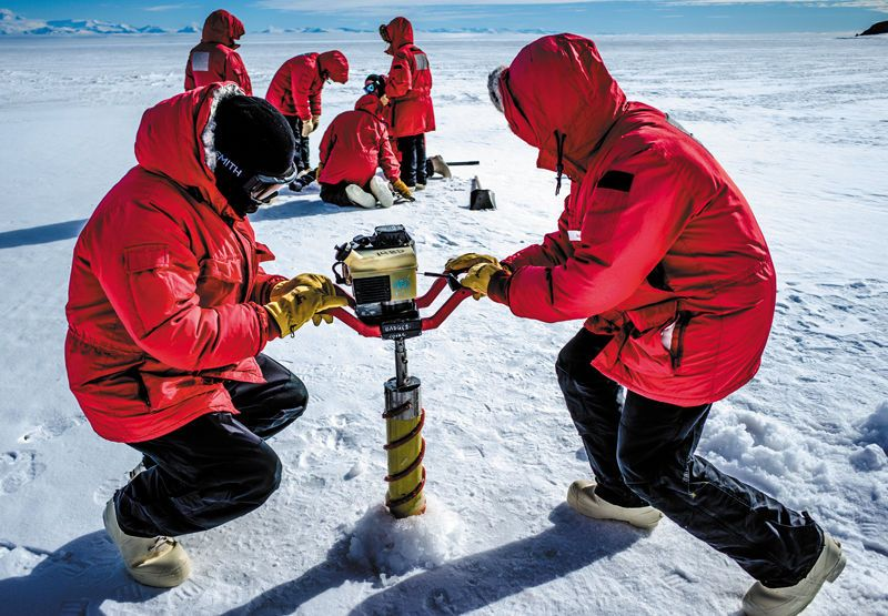 Drilling ice cores. Junior scientists heave up an icecore