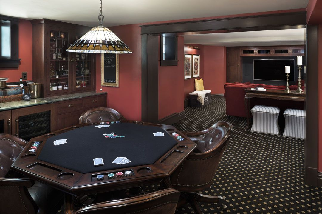 Dark romantic basement with built-in bar, poker table, and media