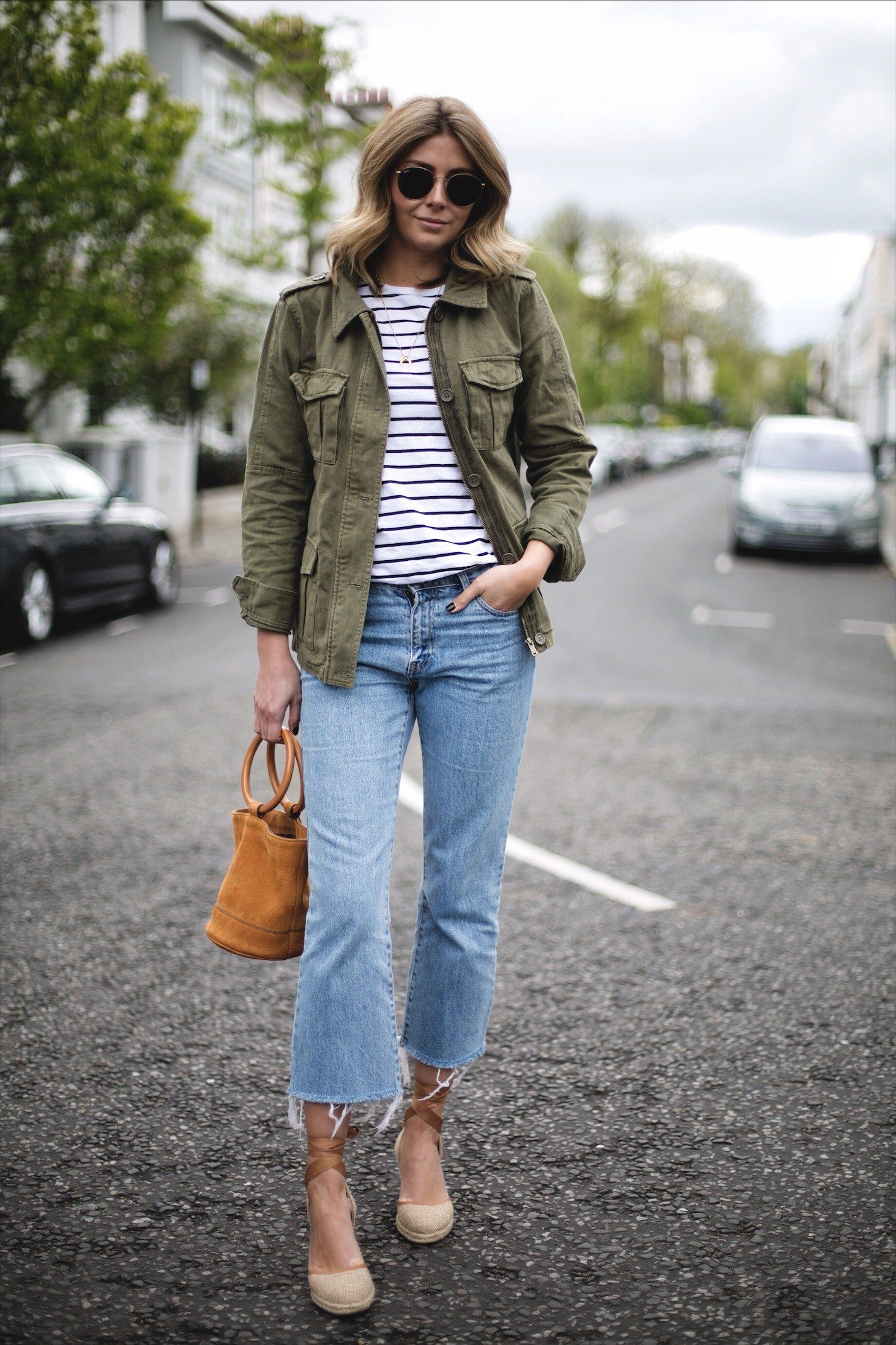 7e68c6c1290 Emma Hill wears khaki utility jacket, black white stripe t-shirt, cropped  flare frayed hem jeans, canvas wedge espadrilles, Simon Miller tan suede  Bonsai ...
