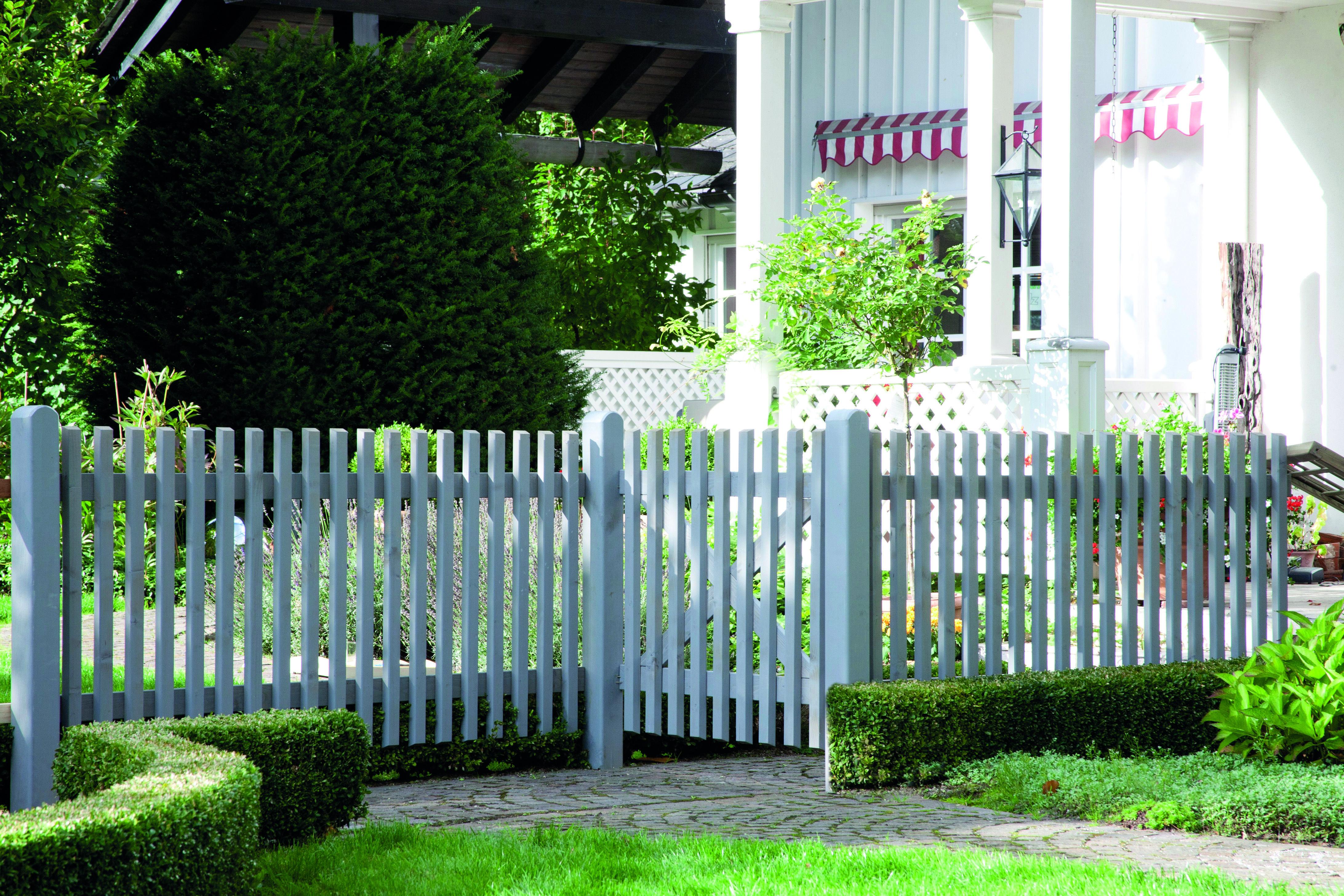 Eine kurze und weiße Holz Zaun umschließt bunte Stiefmütterchen