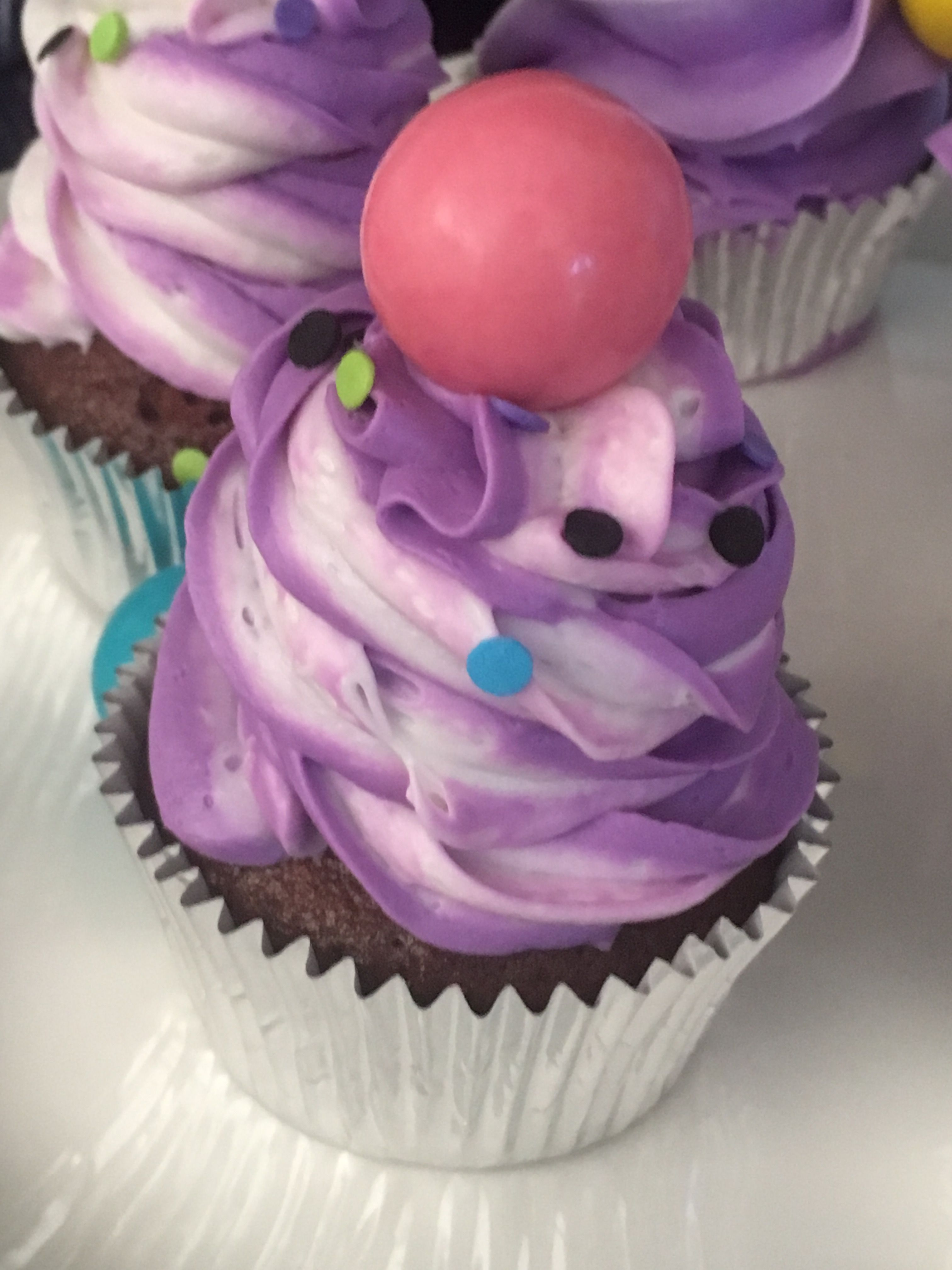 Chocolate cupcakes filled with marshmallow cream and topped with purple and white marshmallow frosting and a gum ball