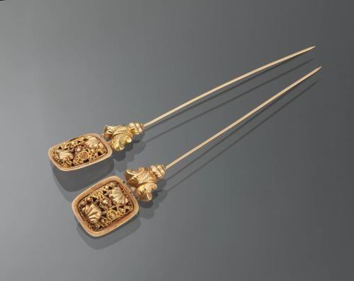 Paar gouden mutsenspelden, Blaricum, circa 1845-1880 | Collectie Gelderland Aaltje de Graaf-Koppen uit Blaricum droeg deze 18-karaats gouden mutsenspelden bij de staartkap. De spelden werden verticaal in de muts gestoken, aan weerszijden van het voorhoofd. Ze zijn tussen 1845 en 1880 vervaardigd door de edelsmid J.F. Umeijer in Amsterdam. De rechthoekige kop van de speld is versierd met open opgelegd cantille. Eronder zit een fleur-de-lis motief. #NoordHolland #Gooi #Blaricum