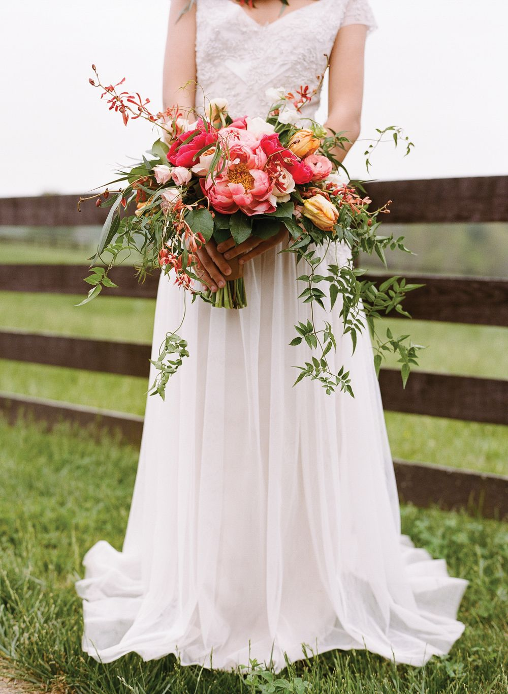 Bride with stunning bouquet in a palette of pink, blush and rust orange including garden roses, tulips, orchids and peonies. Bouquet by Southern Blooms by Pat's Floral Designs, bride's dress by Sarah Janks, image by Jen Fariello.