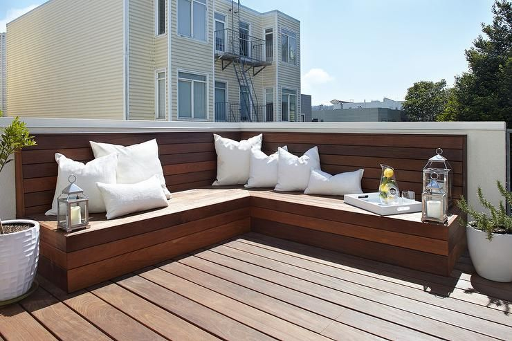 A Stained Deck Boasting A L Shaped Built In Teak Bench Adorned With White Outdoor Pillows Alongsi Diy Bench Outdoor Outdoor Bench Seating Patio Benches Seating