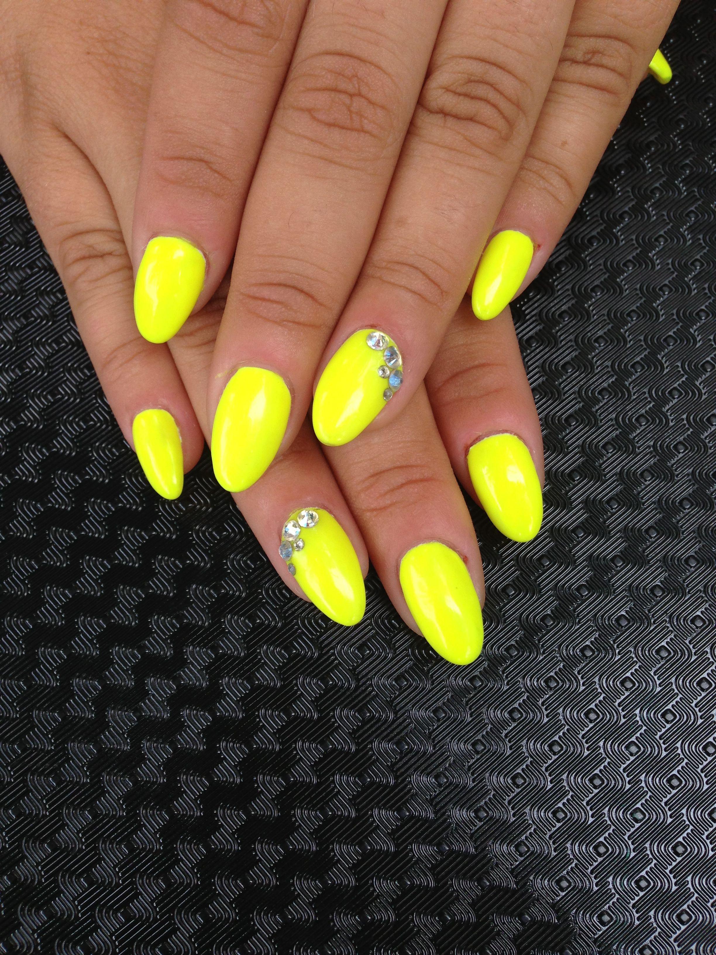 These are stiletto nails, neon yellow with Swarovski crystal detail ...