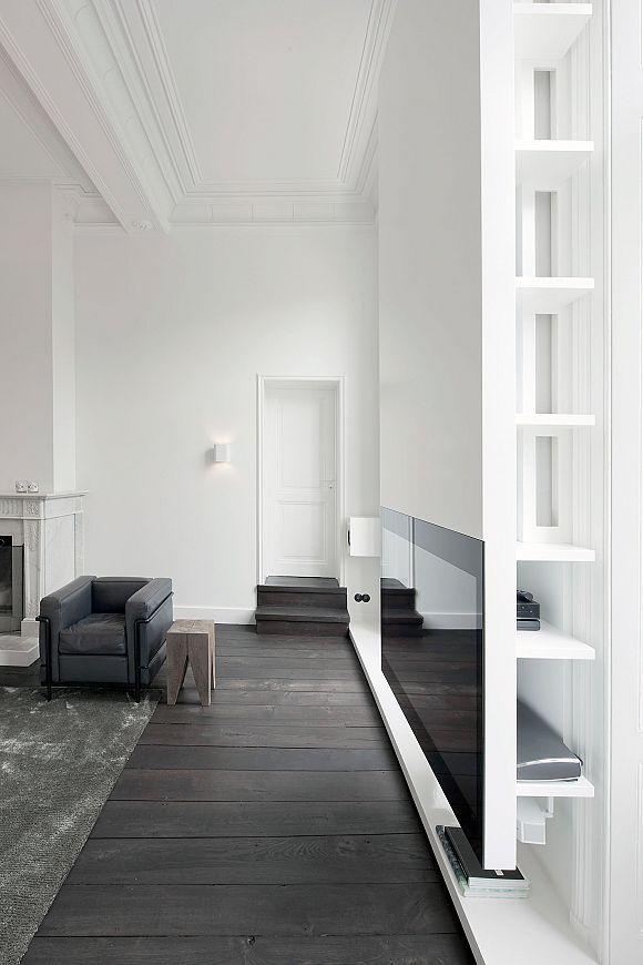 Salón decorado con paredes blancas y muebles en tonalidades grises ...