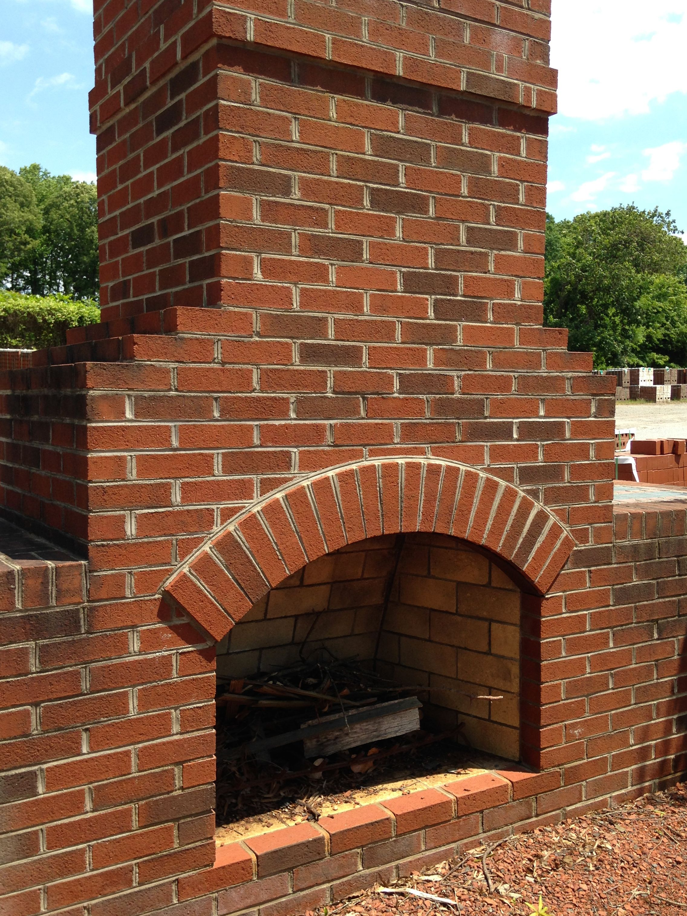 A Classic Outdoor Fireplace Constructed Out Of Old Colonial Style Brick With A Light Grey Mortar