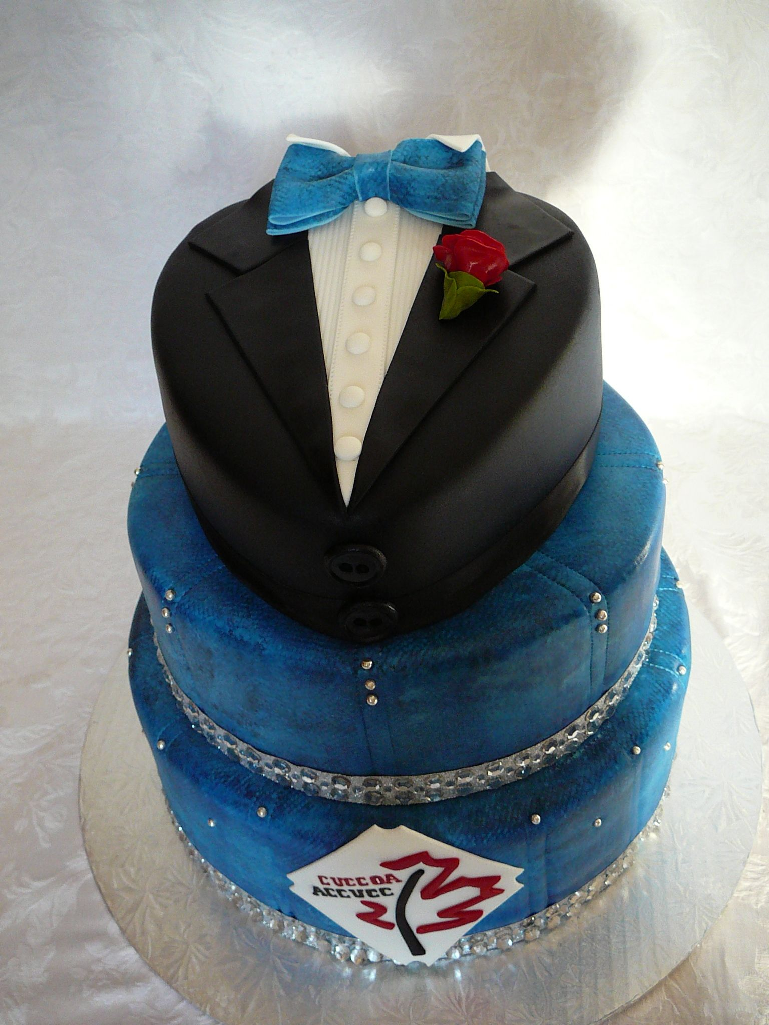 Denim and diamond with tuxedo - I create a cake with theme Denim and Diamond. I was very pleased with the result of my denim effect that I painted on fondant using my own technique that works pretty well. I used fabric ribbon on which I glued one by one the stones... Time consuming but the result is what I wanted. This was a chocolate cake with custard filling, chocolate ganache frosting covered with fondant.