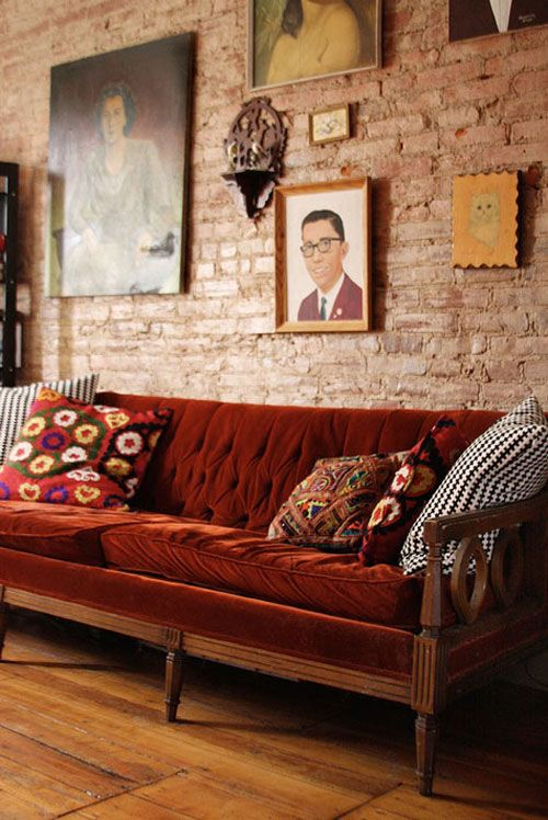Great velvet sofa, thrift store wall art, and hardwood floors. Exposed brick  wall adds to the unique character of this room.