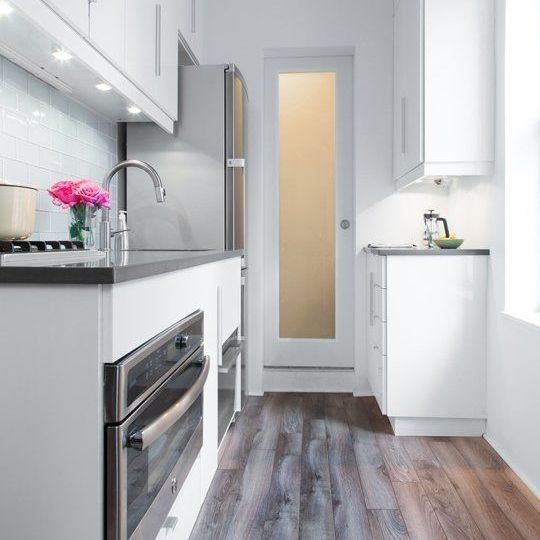 There's nothing boring about neutrals when they look this good! We love how the white cabinets and grey countertops make this wood flooring pop!