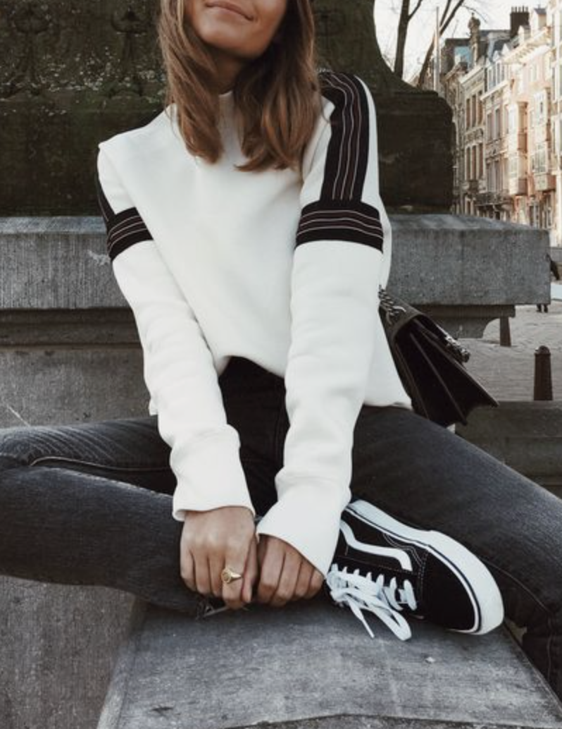 Black jeans, white sweatshirt with black stripes on