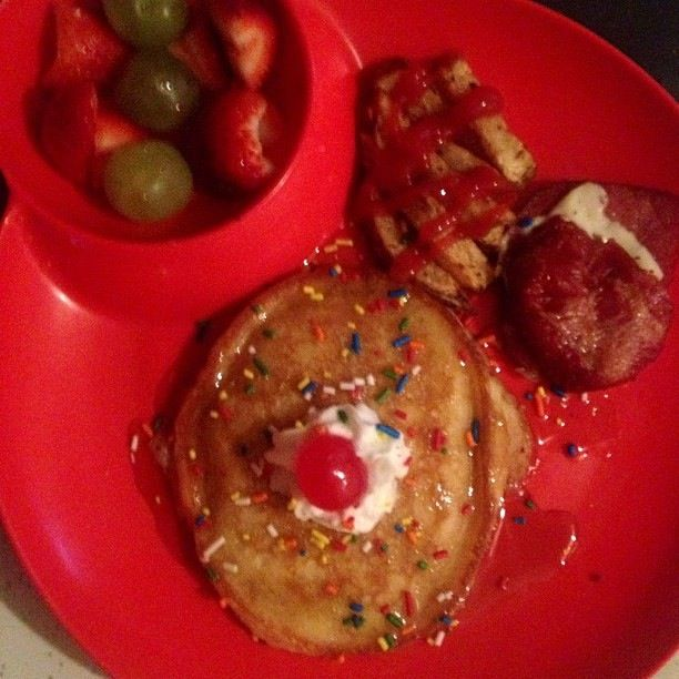 pancakes topped with syrup rainbow sprinkles whipped cream and a cherry on top side of grapes and strawberries and fried fried salami food rainbow sprinkles pinterest