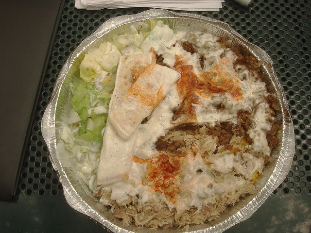 "chicken and lamb over rice plate from Famous Halal Guys on NW Corner of 52nd & 6th Ave. ""same exact food you get on 53rd and 6th (good yellow rice, super hot hot sauce, and very finely chopped meats.)"""