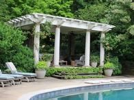 This elegant poolside pavilion uses a canopy of trees and plantings on the stair risers and in containers to blend the architecture with the surrounding landscape.