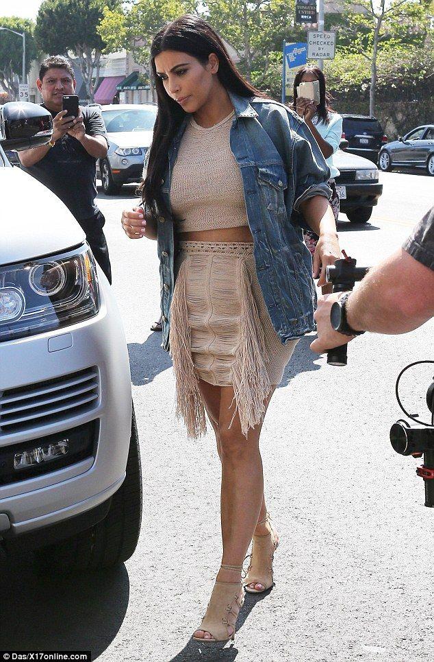 Kim Kardashian flashes her taut tummy in midriff-baring