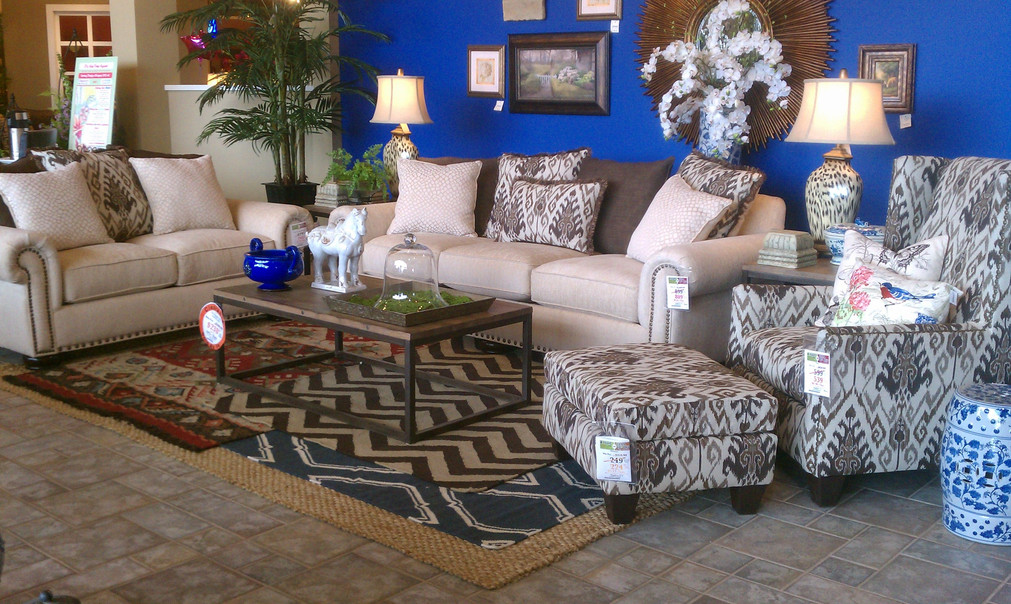 Light sofa loveseat and print accent chair against a beautiful blue