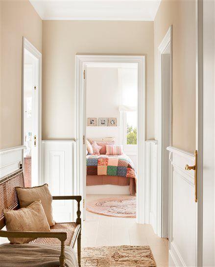 Pasillo en color crema con salpicadero blanco y dormitorio infantil al fondo