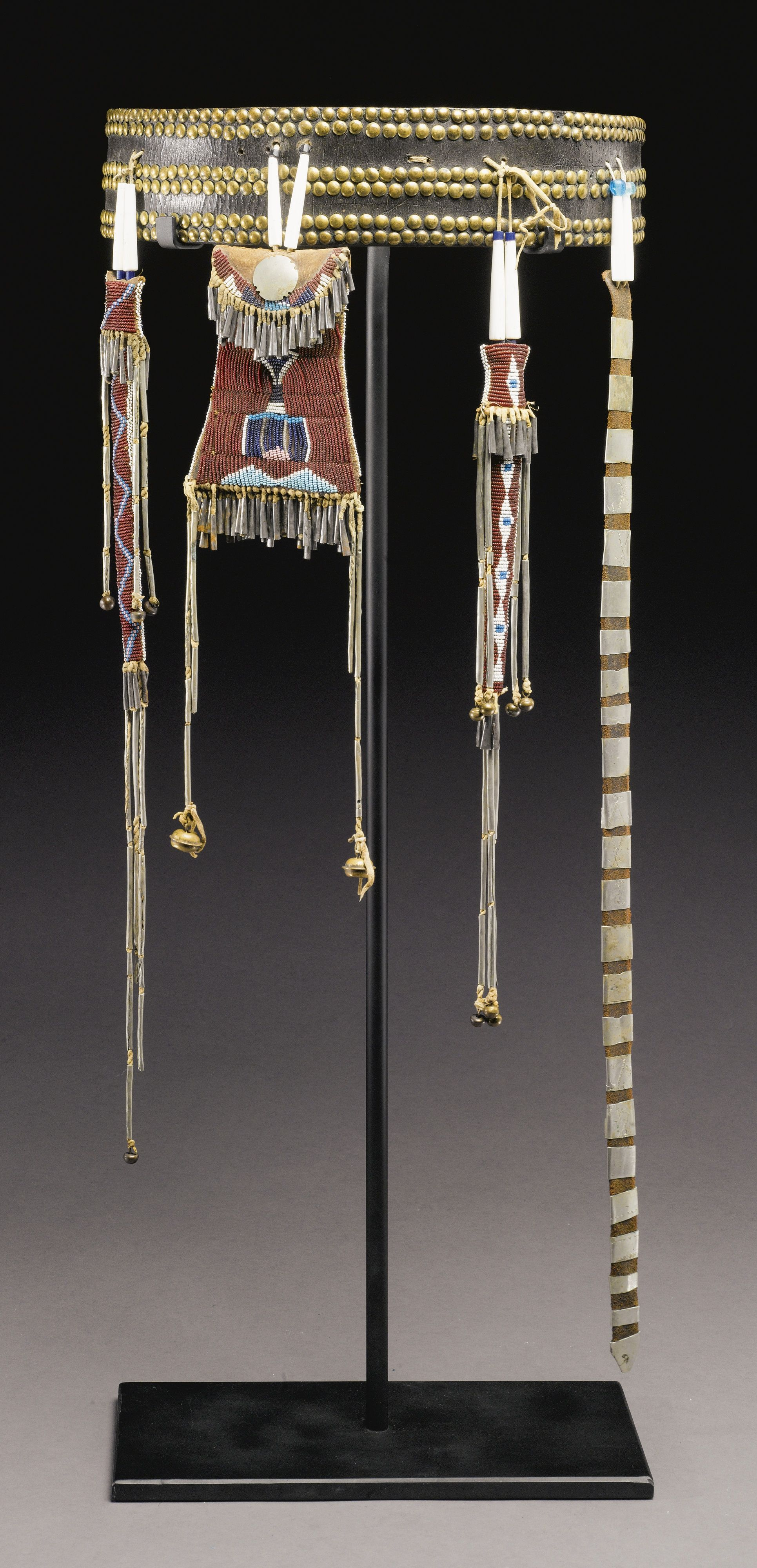 KIOWA WOMAN'S BELT AND BEADED HIDE ACCESSORIES comprising a commercially tanned hide belt, decorated with brass tacks, together with a strike-a-light with German silver button, and two awl cases with hawk bells, each stitched in typical colors against a maroon glass beadwork ground, with geometric motifs, trimmed with long cut hide pendants strung with tubular brass beads, also with a hide belt (fragment?), wrapped with silver slides, some finely incised with scrolling and linear details.