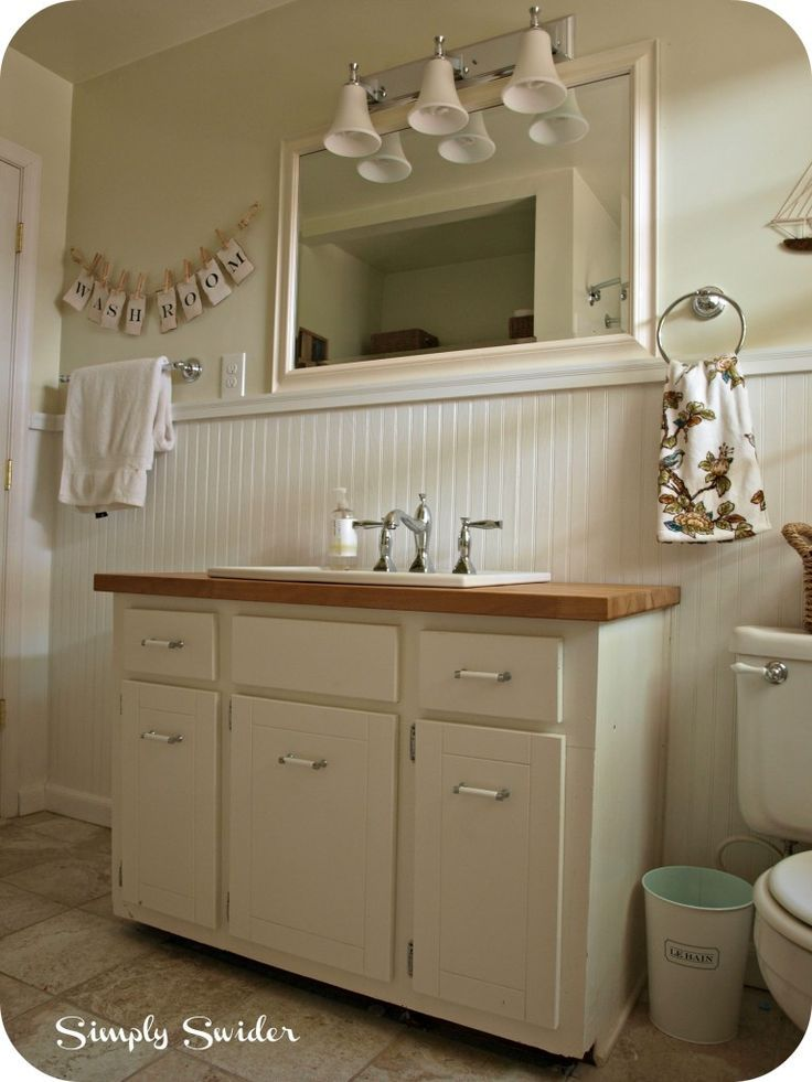 Pictures In Gallery Inn at Little Pond Chic cottage bathroom features white beadboard backsplash framing framed mirror with shelf flanked by oil rubbed bronze quatrefoil