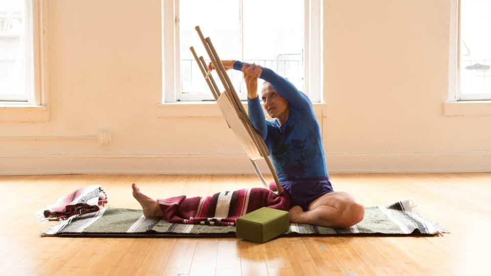 Find Your Most Grounded And Spacious Parivrtta Janu Sirsasana With A Chair Iyengar Yoga Yoga Shoulder Iyengar