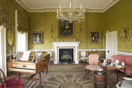 a photo of a formal drawing room with Georgian portraits piano