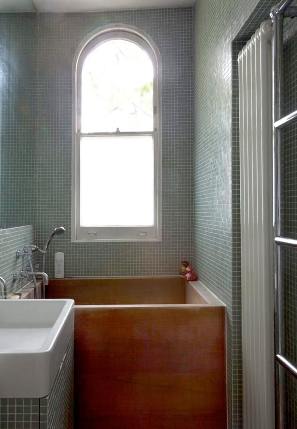 small bathroom with wooden bathtub and light green mosaic everywhere