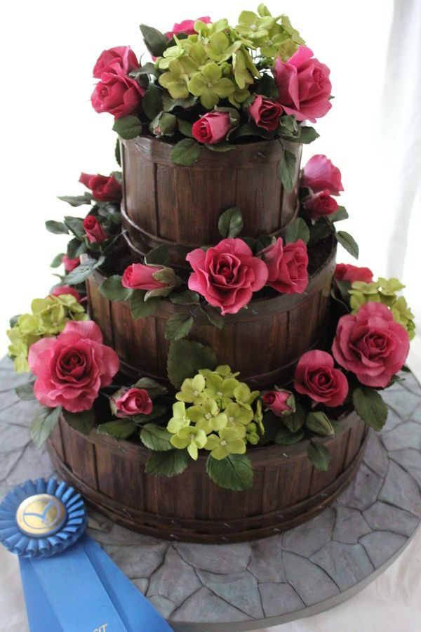 Flower Basket Wedding Cake  Fondant wood grain slatted basket with roses and hydrangea flowers.  Stone fondant cake board.  1st Place NCACS 2013 Professional Wedding Cakes.