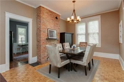Brick Fireplace In Dining Room With Upholstered Chairs