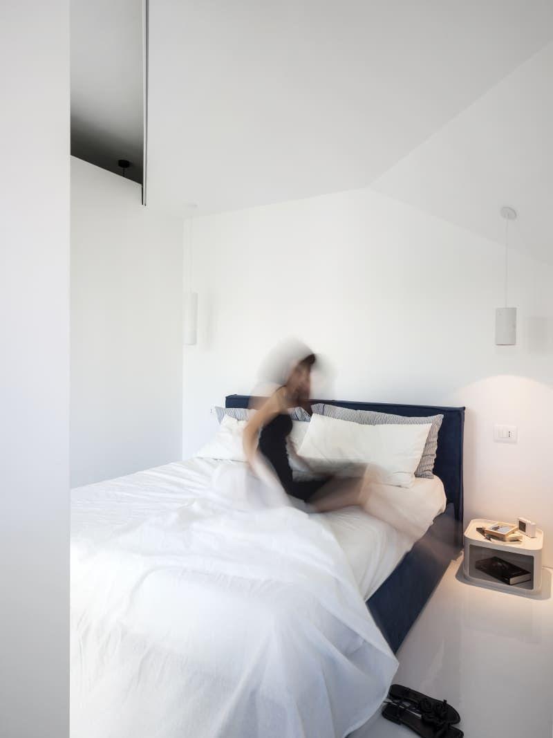 Dans cette chambre toute blanche, le coloris bleu du lit, permet d ...