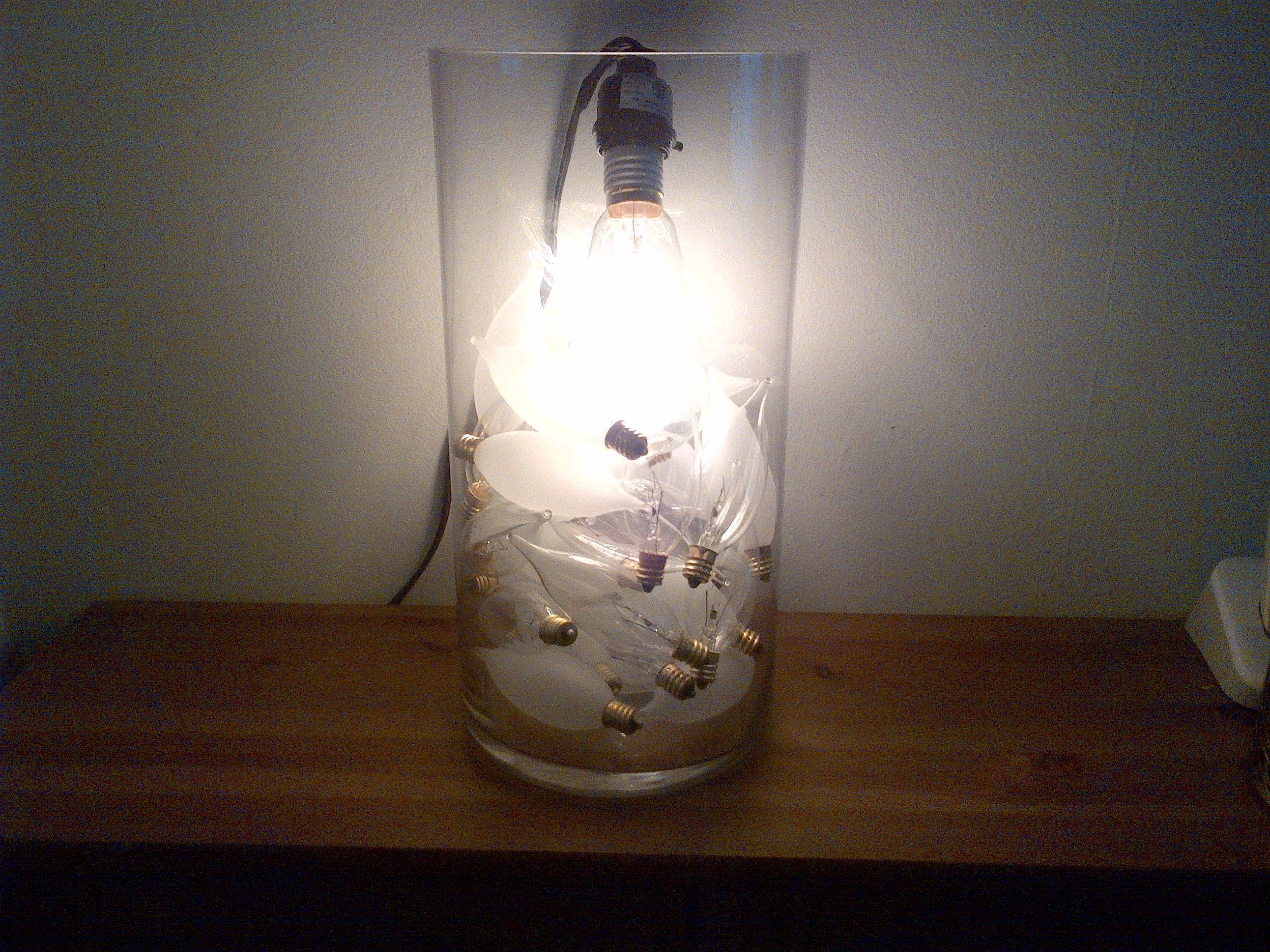I was inspired while shopping in a high end furniture store. A similar light was on display and priced well over $100.00, however could be made for as little as $14.00, if you recycle materials around the house, or if you need to purchase, about $60.00.    All you need is a tall hurricane vase, bulbs (I used 32 frosted and clear), an Edison bulb, and a clamp lamp. A different way to shed light on the situation!