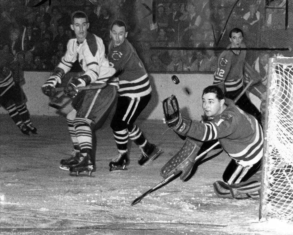 Most of the shots during the Blackhawks vs. Maple Leaf game at Chicago Stadium on Dec. 20, 1959, were aimed at Toronto's Ed Chadwick, but Hawks goalie Glenn Hall, right, did have some business. Hall staves off a shot by Bill Harris, left. Hawks Defensman Pierre Pilote attempts to block Harris while Chicagoan Ed Litzenberger (12) looks on. Hawks won 7-4.