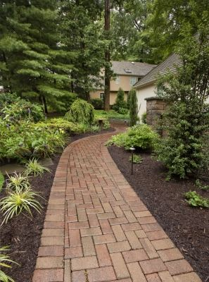A Front Walkway In A Herringbone Pattern With A Complimenting