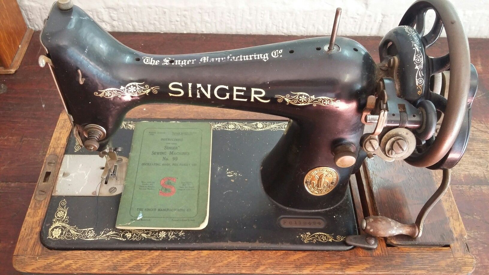 A 1910 Singer sewing machine with spools and instruction manual serial  number F6118494