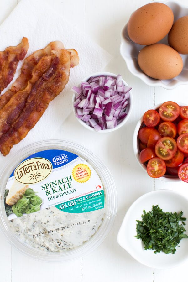 A delicious breakfast omelet made with spinach and kale dip, tomatoes, bacon and onions!