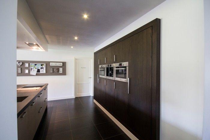 Moderne keuken met ingebouwde kast met inbouwapparatuur eiken donker gelakt gecombineerd met - Keuken licht eiken ...