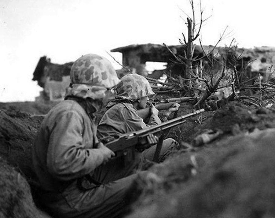A couple of Marines fighting on Iwo Jima armed with an M1 Garand rifle and an automatic rifle M1918 BAR.