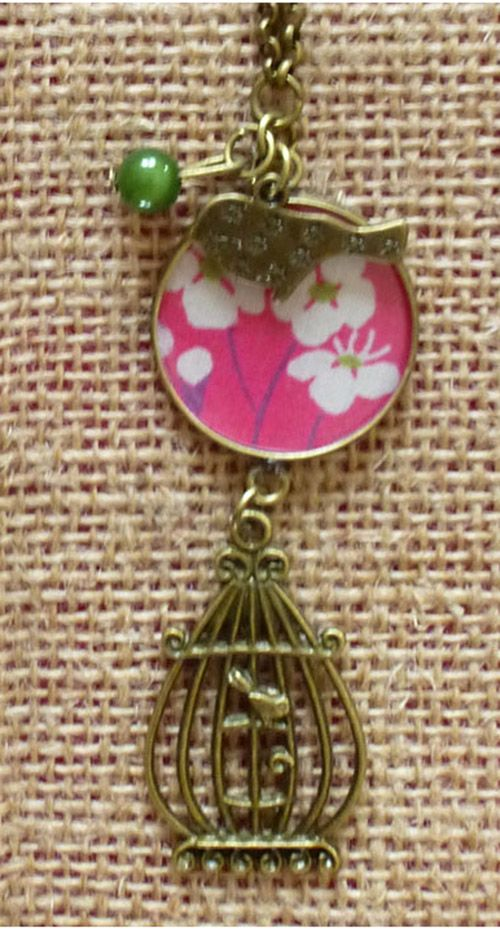 Sautoir en chaine couleur bronze maille ronde 2.5 mm,agrémenté d'un cabochon (2.5 cm) de résine sur un tissus liberty mitsi fuchsia orné d'un petit oiseau, d'une cage à oiseau et d'une perle verte.   Vous pouvez assortir ce collier avec des grandes boucles Ce sautoir est idéal pour égayer une tenue... longueur totale de 45 cm porté.   Garantie sans nickel,sans plomb