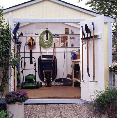 Shed Door Open To Show All Of The Different Gardening Tools In The Shed