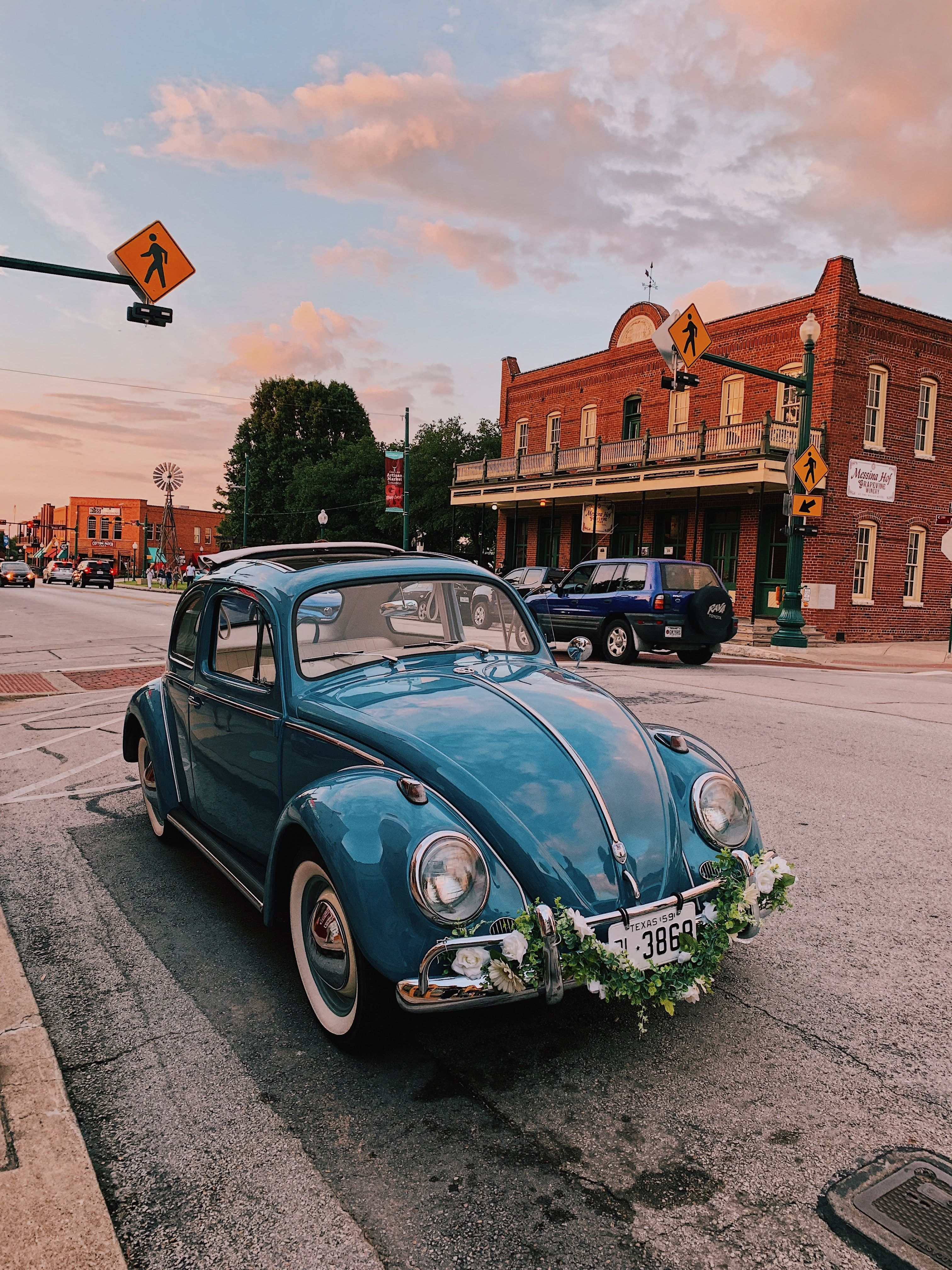 Blue Vintage Old Volkswagen Beetle In Small Town Square With