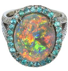 Fine black crystal opal, Paraiba blue tourmaline and diamond ring Centering one oval cabochon black crystal opal measuring