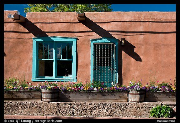 Adobe facade with flowers, windows, and vigas shadows  Santa Fe, New