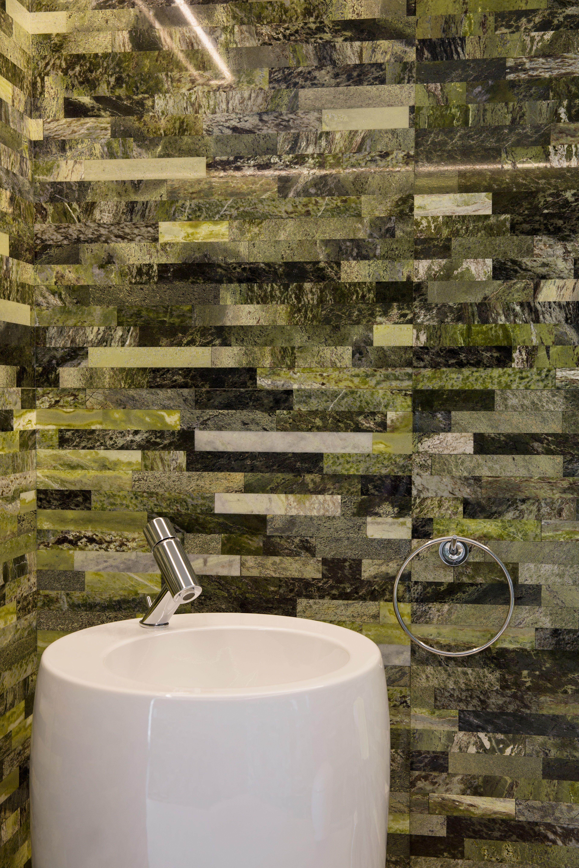 Das Waschbecken im WC vor der grünen Natursteinwand befindet sich